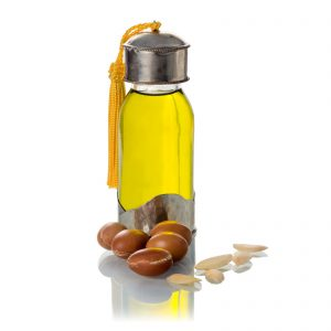 13443451 - argan oil, with fruits and seeds on a white background